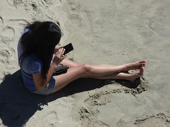 woman on beach using phone