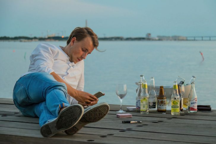 person using their phone while drinking upscaled