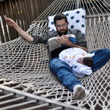 man laying in hammock with baby
