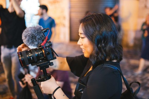 woman filming with a camera